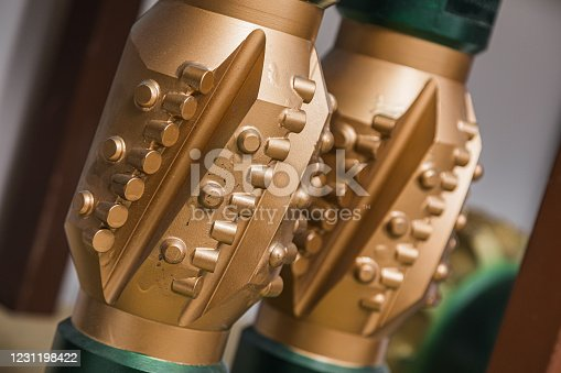 Drill Bits on shelving in stock. Oil drilling equipment for workover. Golden color rock drilling bit. Brand new PDC Polycrystalline Diamond Compact drilling bit