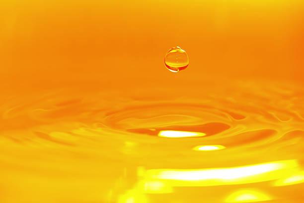 goldene farbe wasser tropfen hintergrund-xxxxxlarge - öl tropfen stock-fotos und bilder