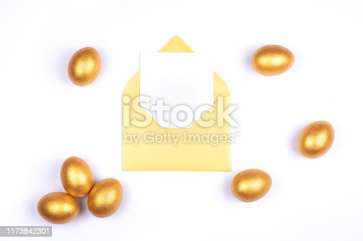 istock Golden colored Easter eggs, blank card in opened golden envelope on white background. Place for text. 1173842301