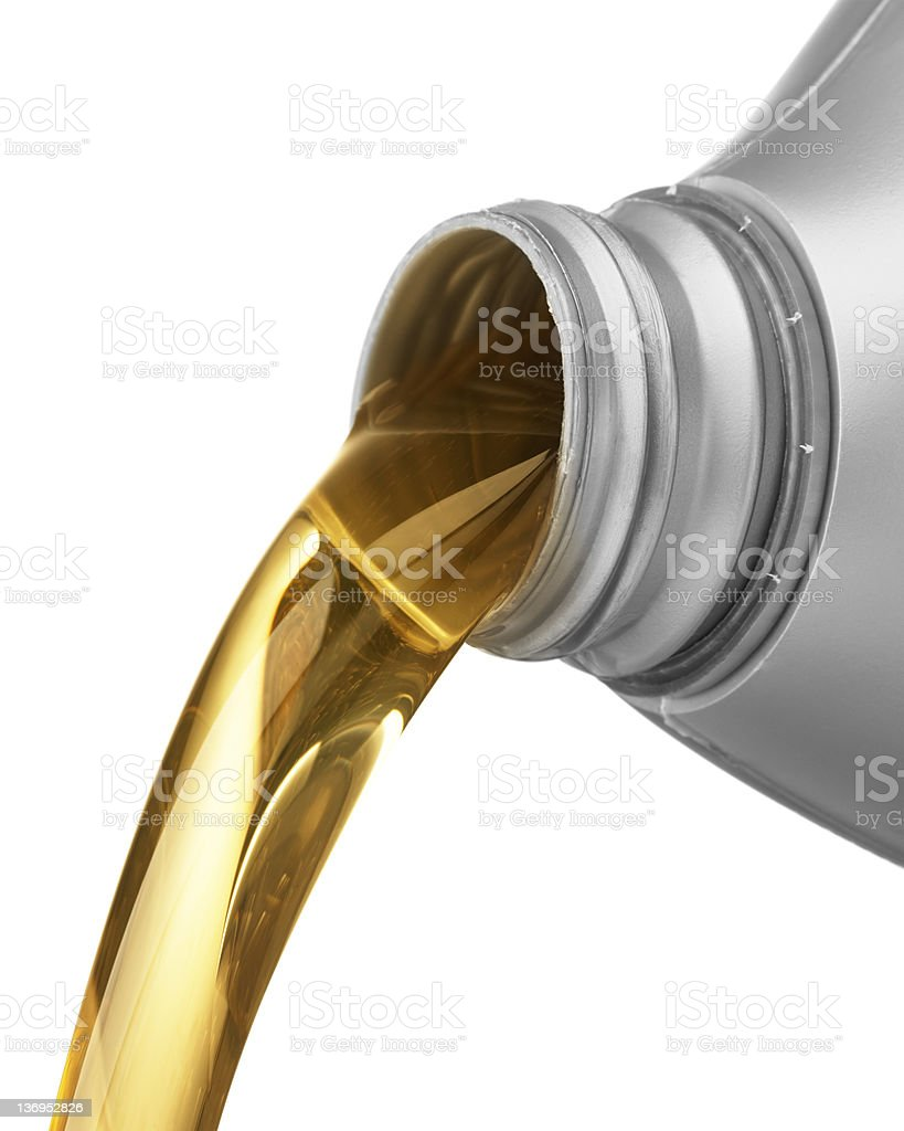 Golden colored oil being poured from a plastic container stock photo