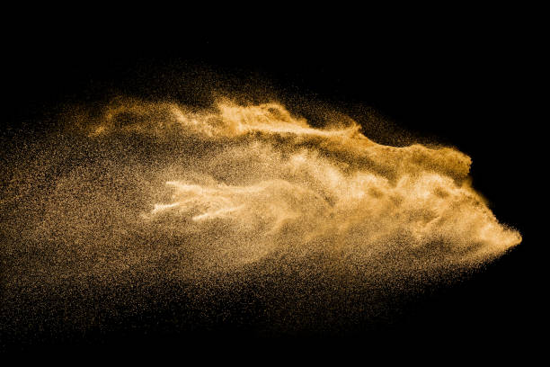 golden colored sand splash against dark background. yellow sand fly wave in the air. - dust stock pictures, royalty-free photos & images