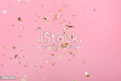 1040055260istockphoto Golden confetti on pink background 939610546