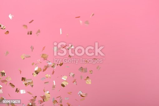 1040055260istockphoto Golden confetti on pink background 939610628