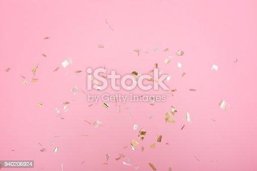 1040055260istockphoto Golden confetti on pink background 940206924