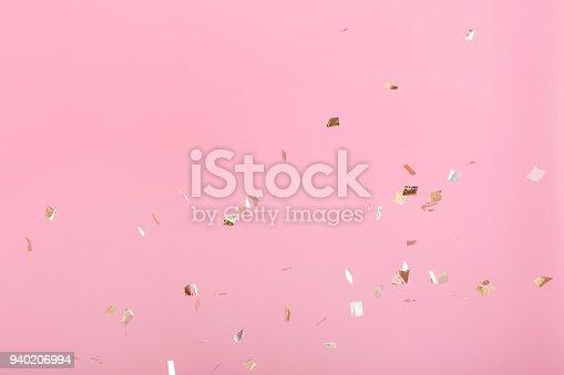 1040055260istockphoto Golden confetti on pink background 940206994