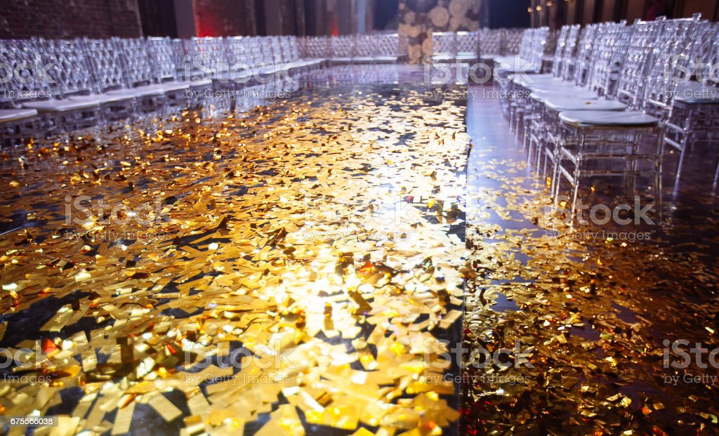 Golden confetti With Sparkling Glitter in fashion exhibition podium stock photo