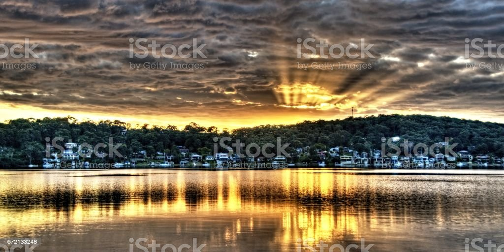 Golden Crepuscular sunrise water reflections. stock photo