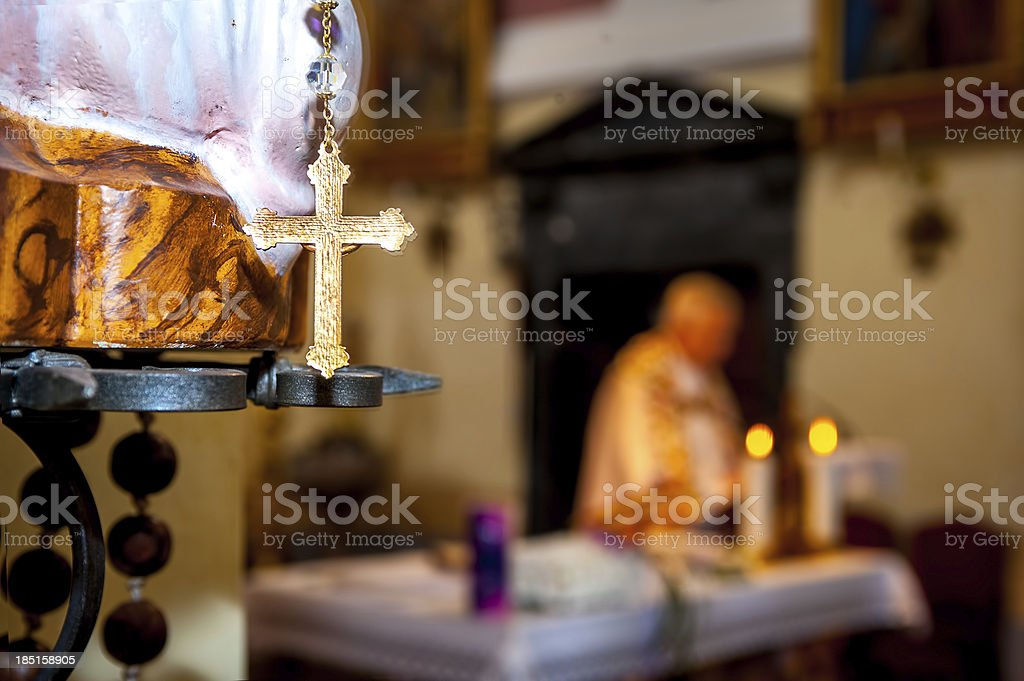 Golden cross close up, with blurred priest during holy mass stock photo