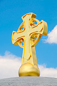 Big golden cross on top of the temple with blue sky in the background