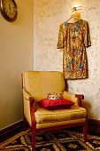 A golden crown encrusted with red and blue gemstones, on a red pillow on a chair in the interior of the room. A gold dress hangs on the wall.