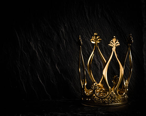 Golden crown with dark background Royal gold crown on dark stone surface. Concept of wealth, success and kingdom. royalty stock pictures, royalty-free photos & images