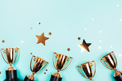 Golden cups of winner with shiny confetti on a blue background with copy space. Flat lay style.