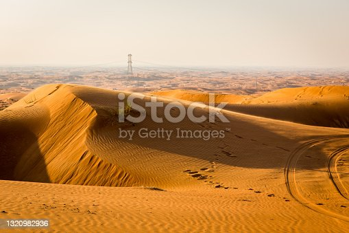 Golden desert dune field landscape with footsteps and transmission towers on the horizon, Fossil Rock, United Arab Emirates.