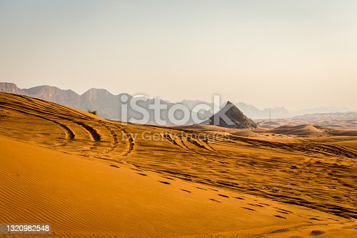 Golden desert dunes with rocky Jebel Al Fayah mountains in the background, footsteps and 4x4 tire tracks on sand, Fossil Rock, United Arab Emirates.