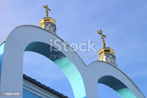 golden domes with crosses on the blue-white arches of the Orthodox church against the blue sky