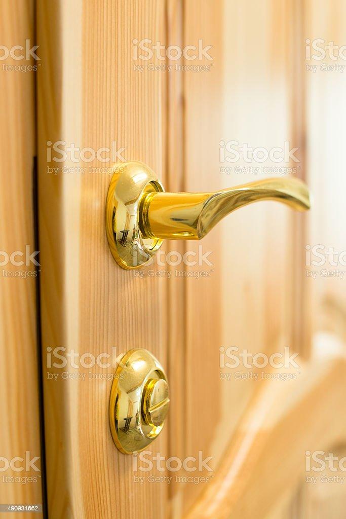 Golden door handle and lock on the wooden door stock photo