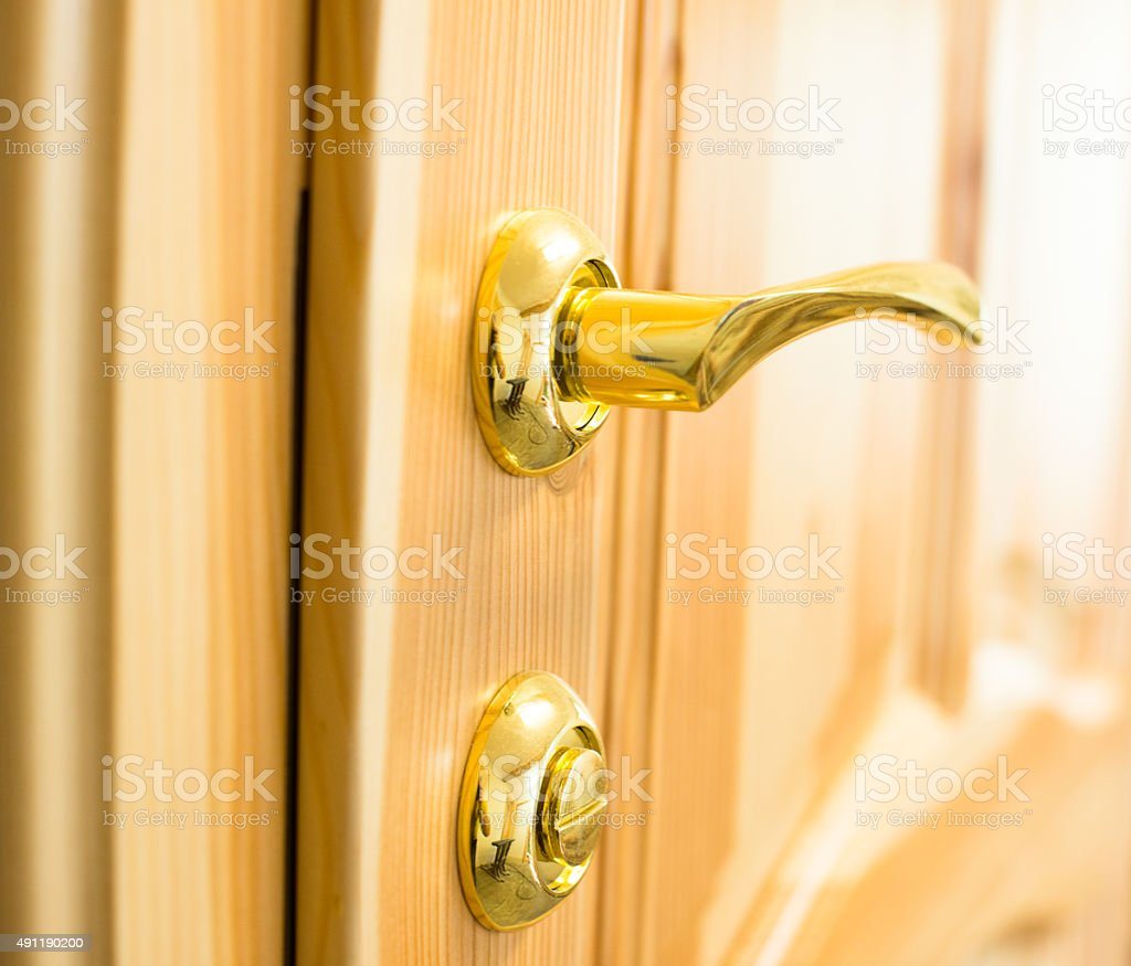 Golden door handle and lock on the wooden door stock photo