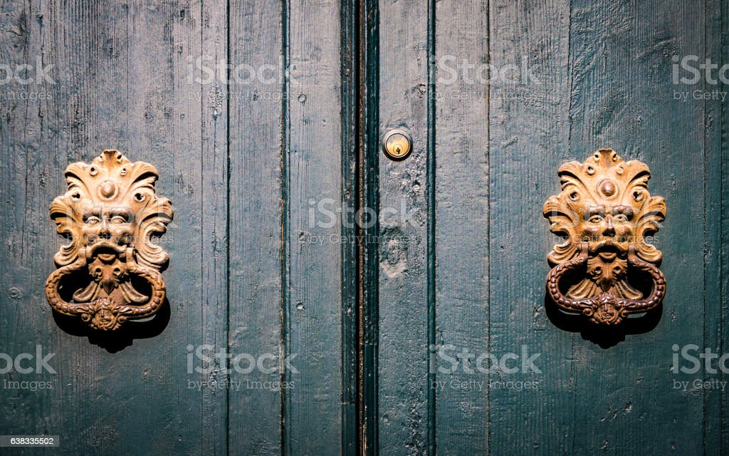 Golden door knockers of an old door in Italy. stock photo