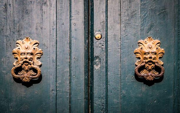 Golden door knockers of an old door in Italy. stock photo