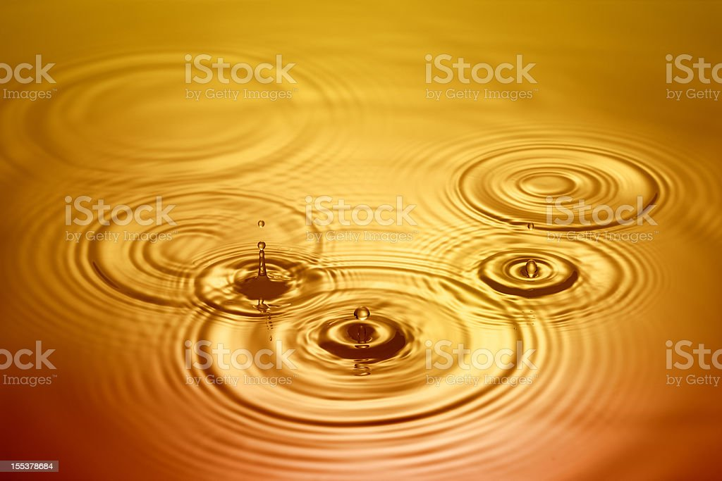 Golden droplets of water falling in to pool royalty-free stock photo