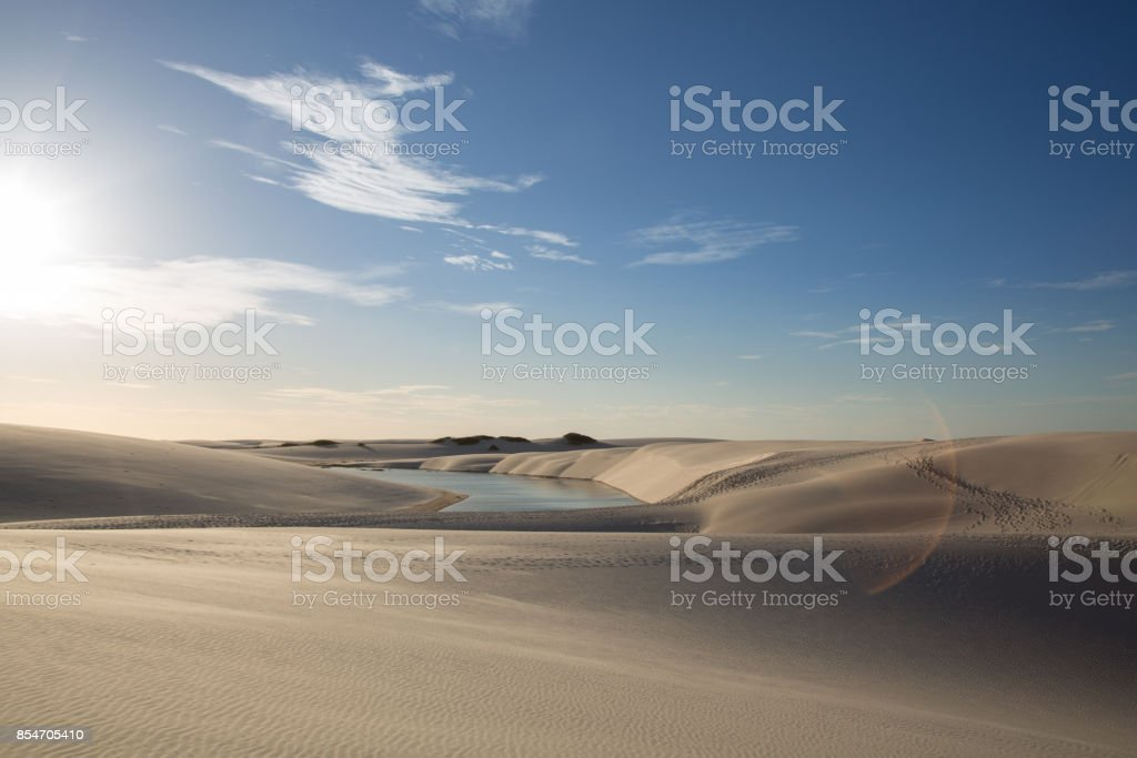Golden dunes at the sunset of the lençois maranhenses with a photo flare stock photo
