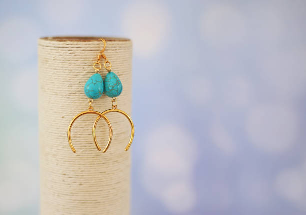 golden earrings with lucky horseshoe and turquoise semi precious stones stock photo