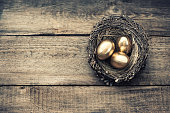 Golden easter eggs in birds nest on wooden background. Vintage style toned picture