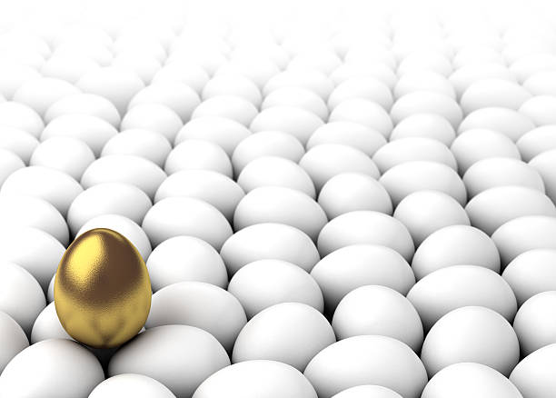 A golden egg on a pile of normal eggs stock photo