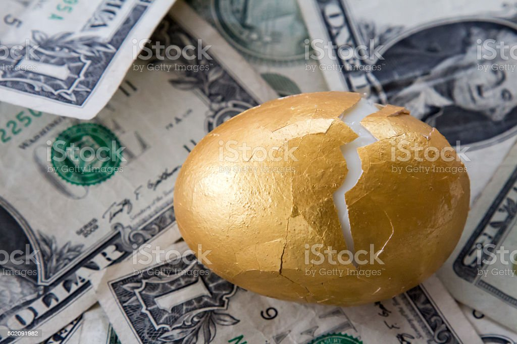Golden egg with cracked shell on money stock photo