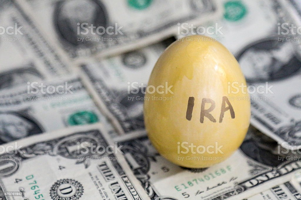 Golden eggs marked IRA on a background of dollars stock photo