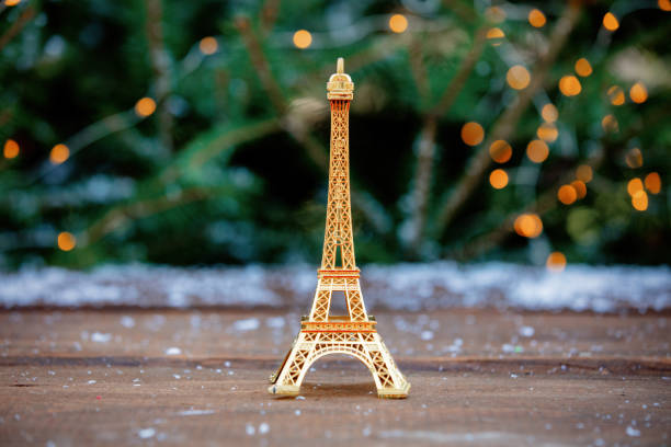 Golden eiffel tower souvenir on table with spruce on background stock photo