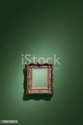Golden empty antique picture frame hanging on green wall