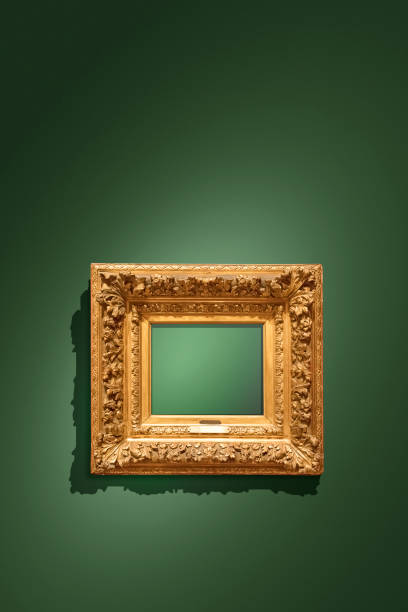Golden empty antique picture frame hanging on green wall stock photo