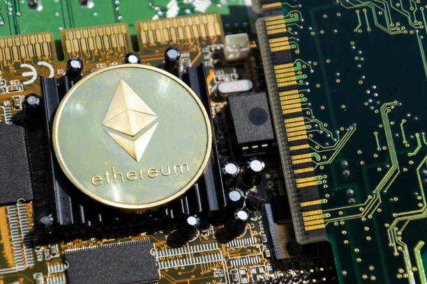 Golden ethereum coin lying on computer motherboard, cryptocurrency investing concept stock photo