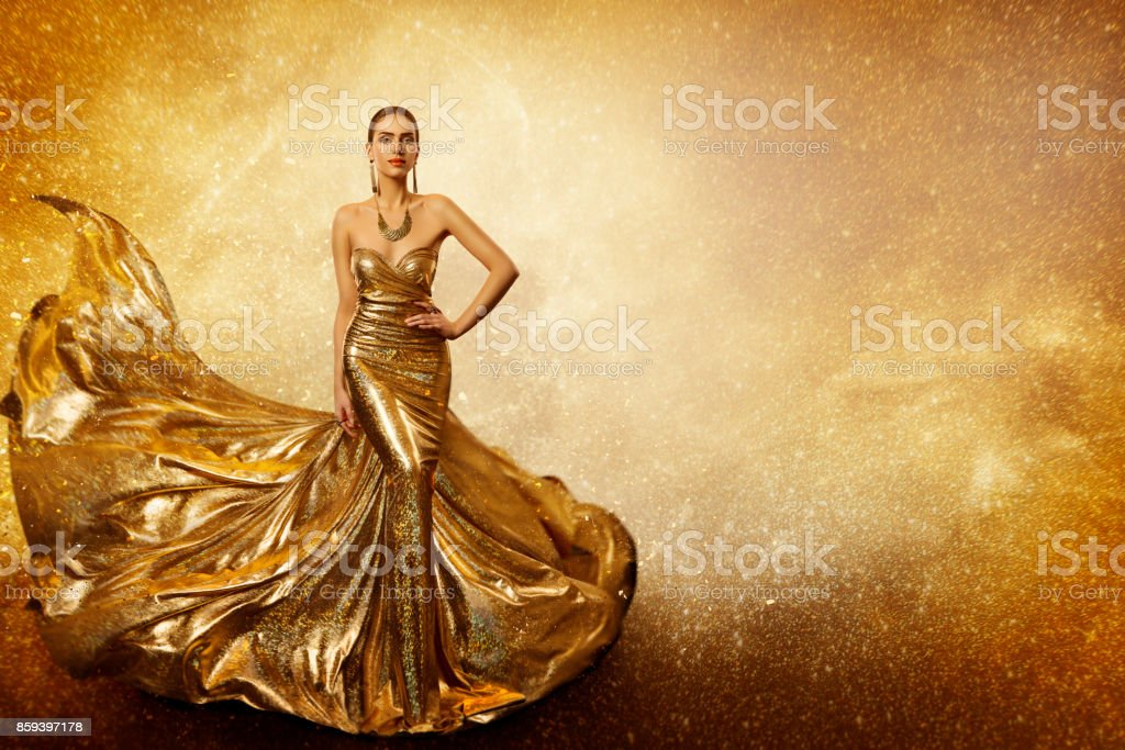 Golden Fashion Model, Elegant Woman Flying Gold Dress, Waving Sparkling Gown Fabric stock photo