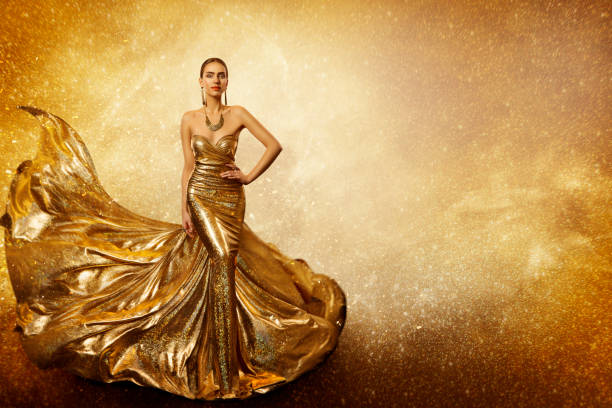 golden fashion model, elegant woman flying gold dress, waving sparkling gown fabric - prom fashion stock photos and pictures