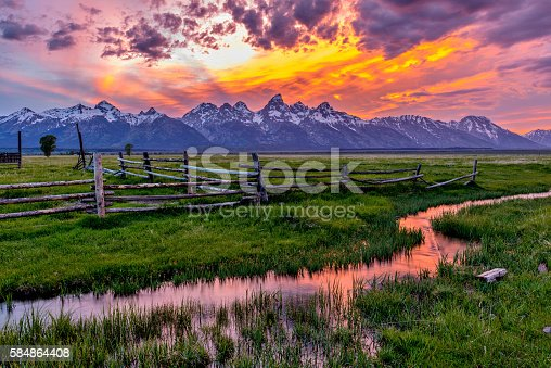 A colorful spring sunset at Teton Range, seen from an abandoned old ranch in Mormon Row historic district, in Grand Teton National Park, Wyoming, USA.