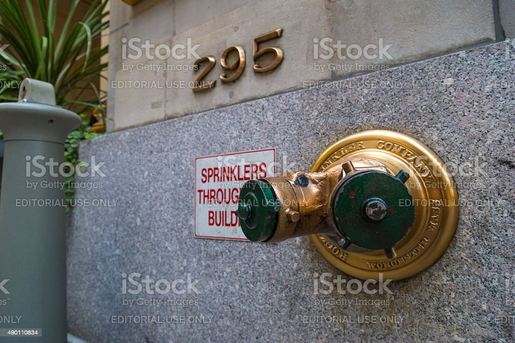 Golden fire hydrant sprinkler connection in a wall in NYC stock photo