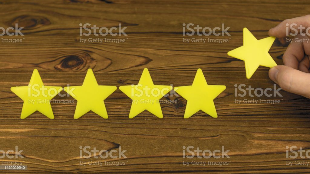 Golden five star shape symbol on wood background. customer service...