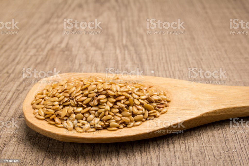Golden Flax seed. Grains in wooden spoon. Rustic. stock photo