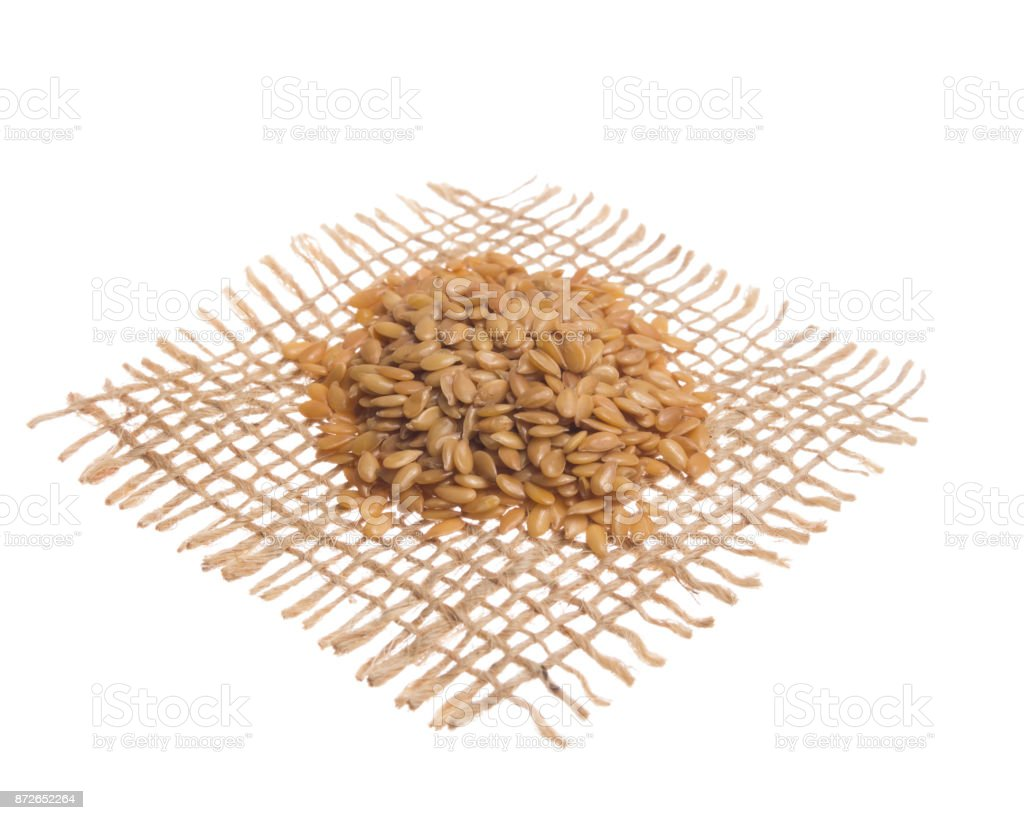 Golden Flax Seed. Grains over hessian fabric, isolated white background. stock photo