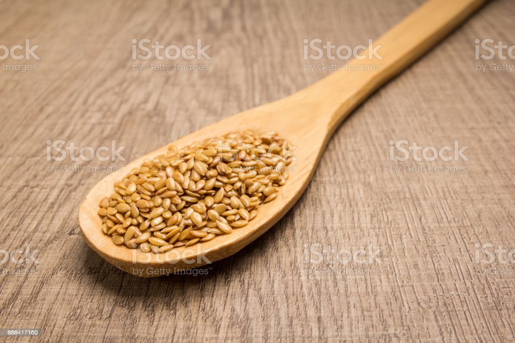 Golden Flax seed. Spoon and grains over wooden table. stock photo