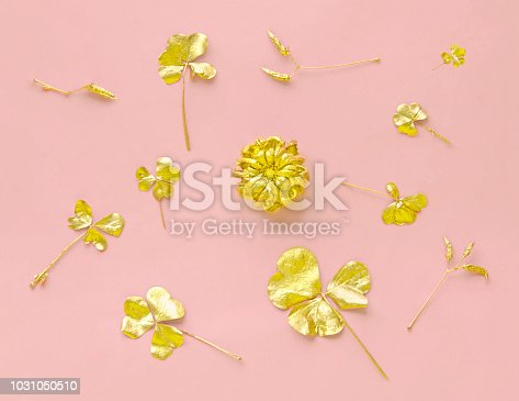 istock Golden flower and clover leaves on pastel pink paper background. Autumn creative concept. Top view. 1031050510