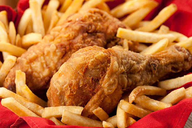 Golden fried chicken on a bed of French fries and red napkin Fried chicken basket. fried chicken stock pictures, royalty-free photos & images