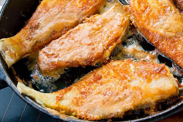 golden fried fish fillets in frying pan - peixe na grelha imagens e fotografias de stock