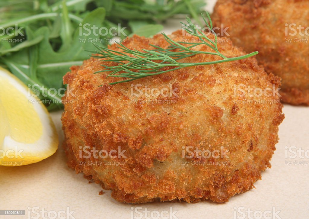 Golden fried haddock Fishcake garnished with lemon and dill stock photo