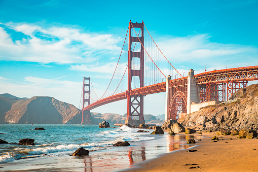 Classic view of famous Golden Gate Bridge in beautiful golden evening light on a sunny day with blue sky and clouds in summer, San Francisco, California, USA