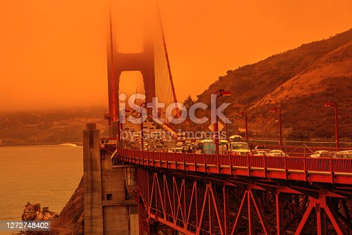 Cars crossing Golden Gate Bridge from Lime point. Smoky orange sky the bridge of San Francisco city for California fires in America. Wildfires composition.