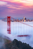 The Golden Gate Bridge rising above a sea of fog with San Francisco skyline in the distance