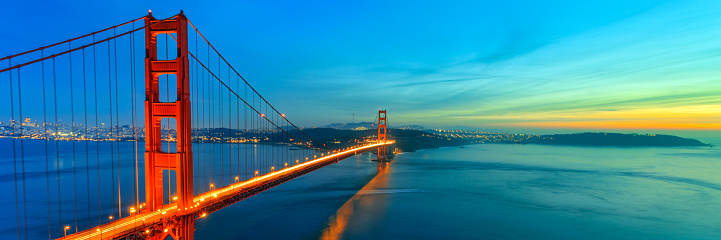 Photograph of Golden Gate Bridge shortly after sunset. This is panoramic view of Golden Gate. Bridge is brightly illuminated and located on left side of photograph with colorful sunset sky.